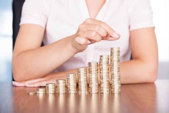 Pessoa conta moedas em mesa: dinheiro, dívidas
