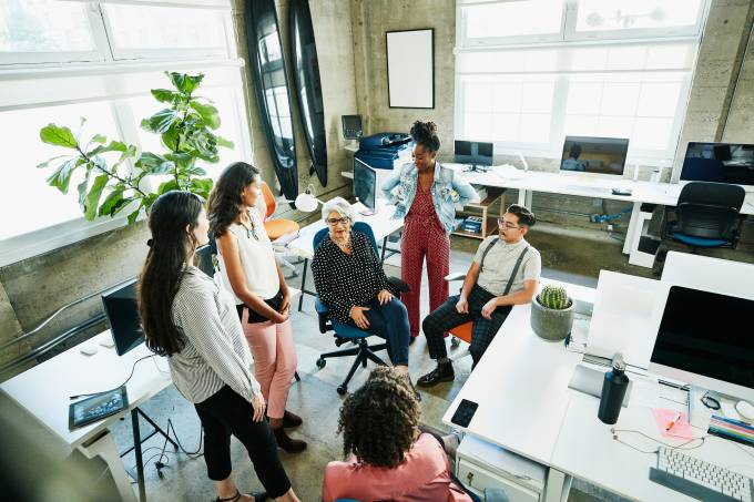 Mature female business owner leading meeting with employees in design studio
