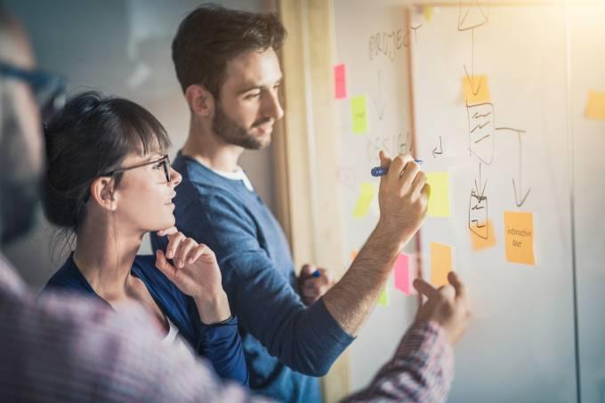 Pessoas/funcionários/empreendedores colam post-it em parede: reunião, planejamento