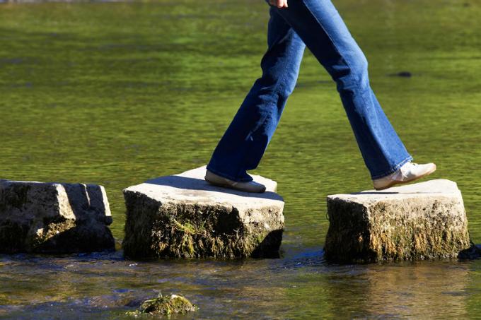 Pessoa pulando pedras