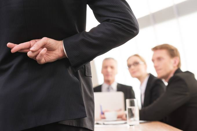 Homem executivo durante reunião com os dedos cruzados nas costas