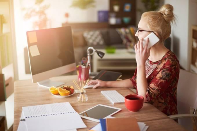 Mulher fala em telefone enquanto usa o computador, o tablet e escreve: trabalhar de casa, home office, home based