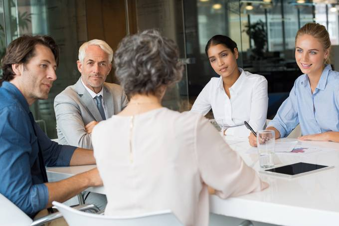 Chefe conversa com funcionários (reunião, feedback)