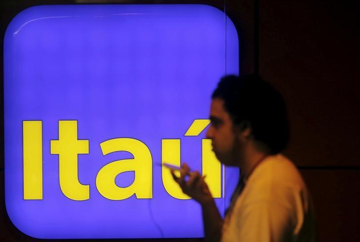 Homem passa em frente a logomarca do Itaú, na Avenida Paulista, em São Paulo
