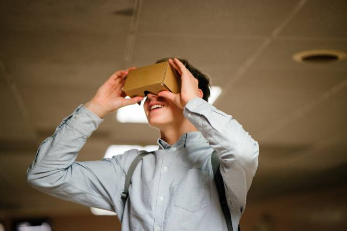 man-in-grey-dress-shirt-using-brown-cardboard-vr-glasses-936575