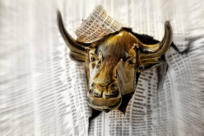 Charging Bull Looking Through Torn Page of Financial Newspaper.