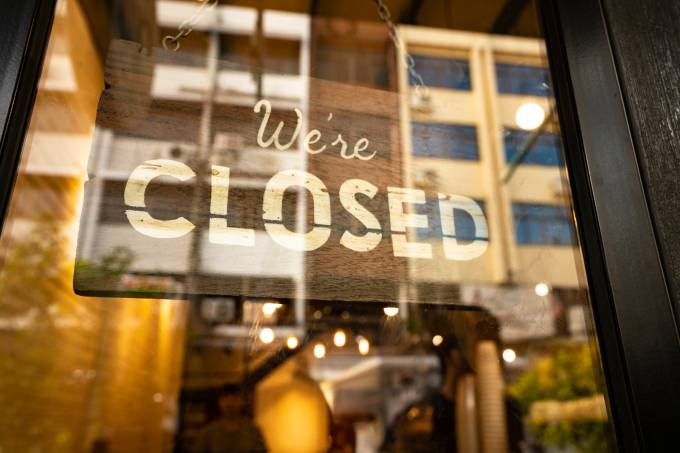 Closed sign hanging in business window by a string – crooked with glob of glue also attaching it to window