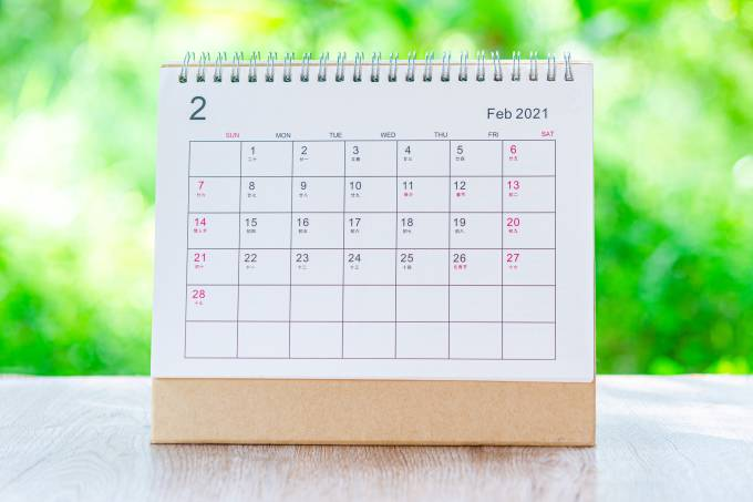 Calendar desk 2021 February month for organizer to plan and reminder on wooden table on nature background.