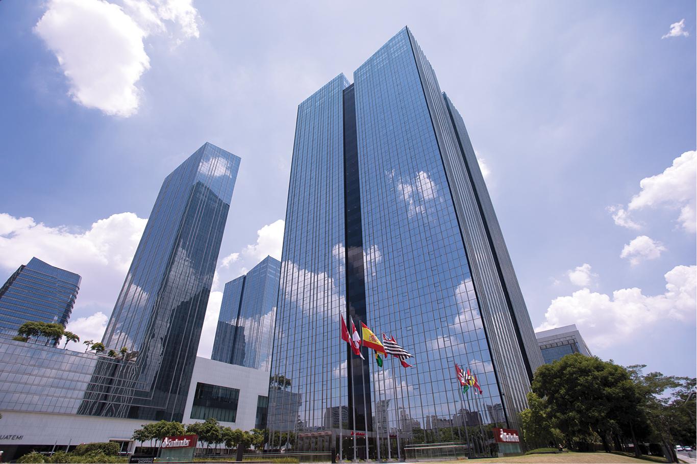 Fachada de um prédio espelhado na região da Faria Lima. Em frente, bandeiras de São Paulo, Brasil e Espanha.